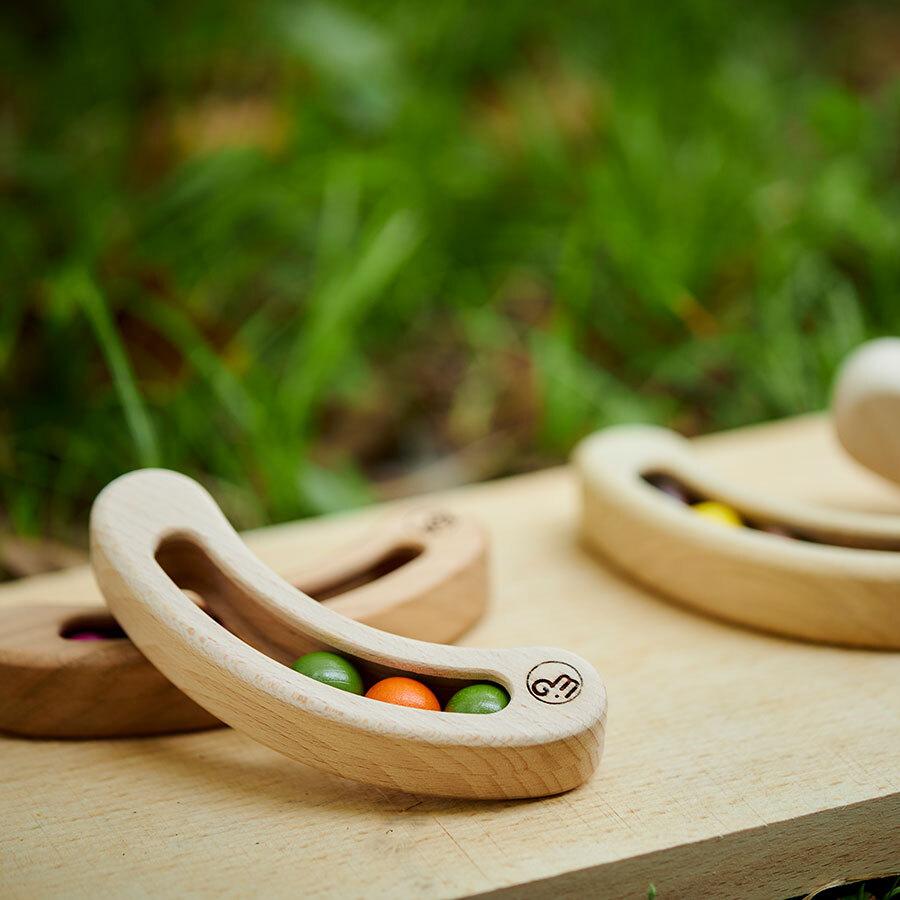 握って、振って、揺らして遊べるラトル「FAVA」。房の中に豆が3粒入ったデザイン。