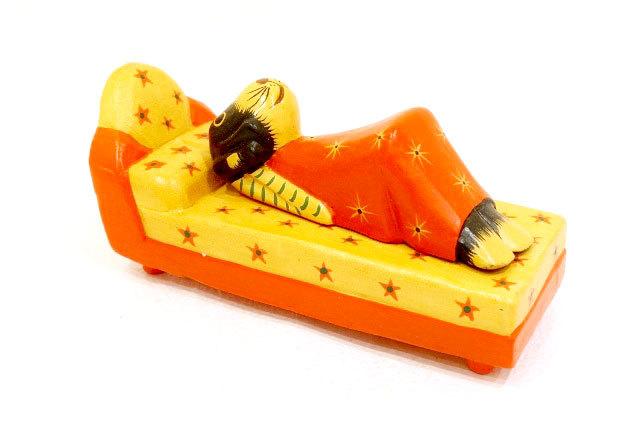 木彫りのバリ人形15 横になり電話するイヌ